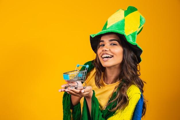 Voetbal promotie. vrouw die een miniboodschappenwagentje in handen houdt die braziliaanse kleren dragen.