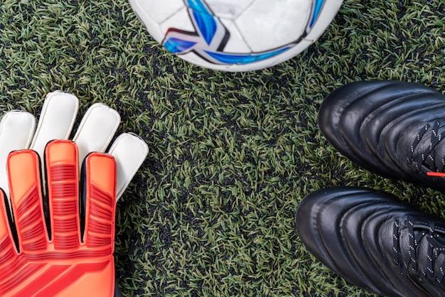 Voetbal stud schoenen met voetbal en handschoen op kunstgras veld