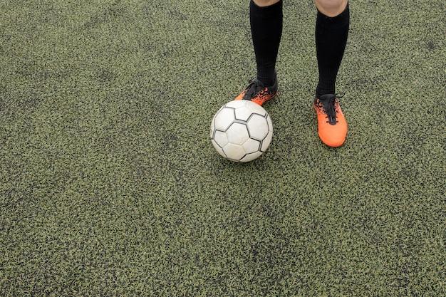 Voetbalbal en voeten op een voetbalgebied