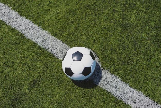 Voetbalbal op groen gras over de witte lijn