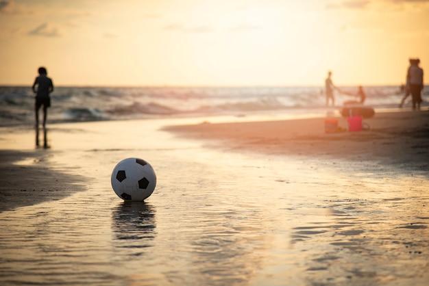 Voetbalbal op zand / speelvoetbal bij het overzees van de strandzonsondergang