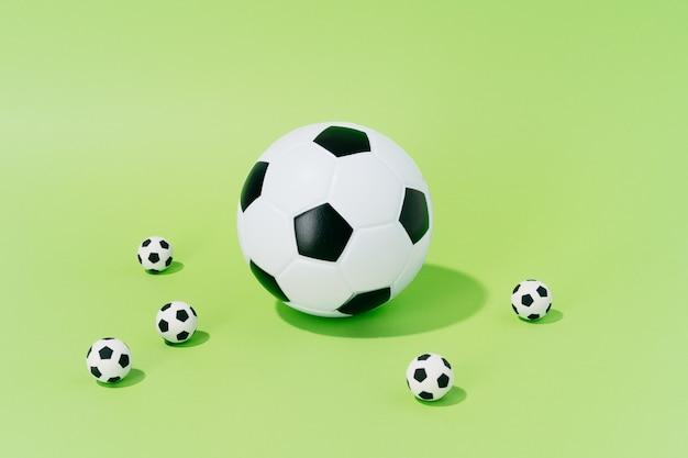 Voetbalballen van verschillende grootte op een groene achtergrond. concept van voetbal en sport.
