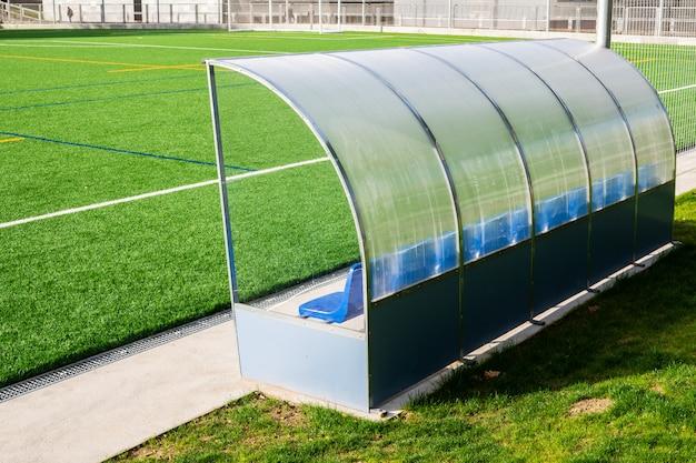 Voetbalbank van een voetbalhof met kunstgras