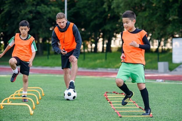 Voetbalcoach kijkt toe hoe zijn leerlingen hardloopoefeningen maken en obstakels overwinnen