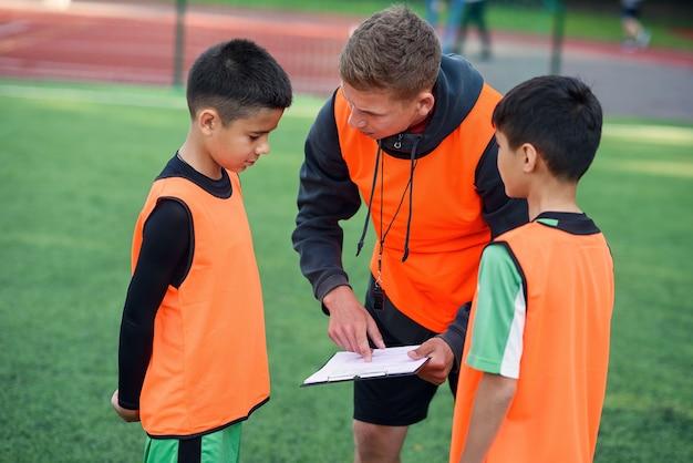 Voetbalcoach toont een strategie van voetbalwedstrijd aan zijn spelers tijdens de training.