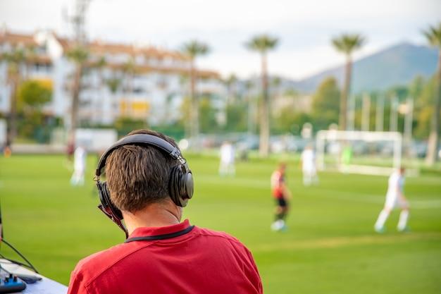 Voetbalcommentator beschrijft het spel live op tv en radio. kopieer ruimte