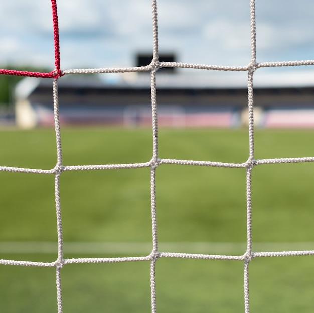 Voetbaldoelen bij stadion. voetbal veld achtergrond. witte en rode netten kleur.