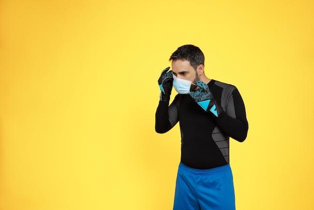 Voetbaldoelman die zijn masker van zijn gezicht verwijdert vanwege de covid19 coronavirus-pandemie op een gele muur