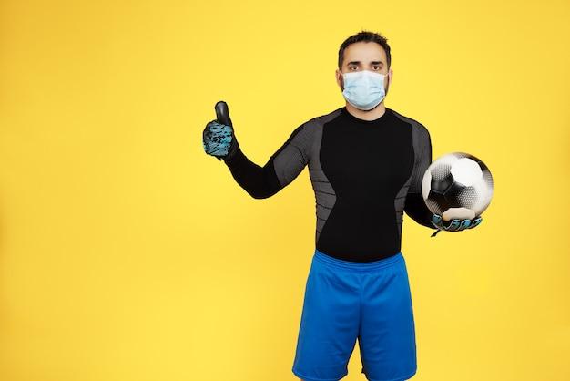 Voetbaldoelman met een masker op zijn gezicht vanwege de coronavirus-pandemie zwaaien met zijn vinger doet het goed en een bal in zijn handen op een gele muur
