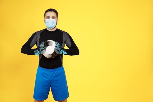 Voetbaldoelman met een masker op zijn gezicht vanwege de pandemie van het coronavirus covid19 met de bal met zijn handen op een gele muur