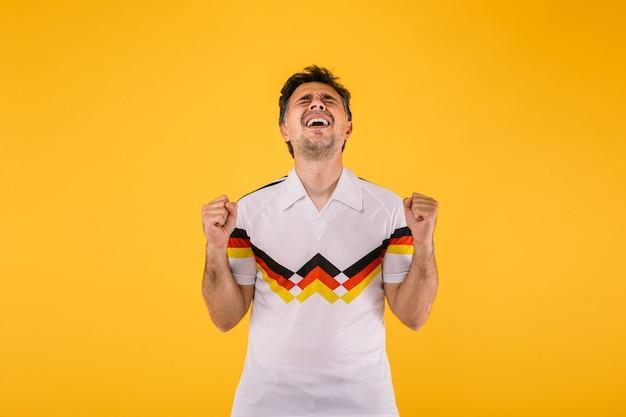 Voetbalfan draagt een wit t-shirt met zwarte, rode en gele strepen, balt zijn vuisten en schreeuwt juichend voor zijn team.