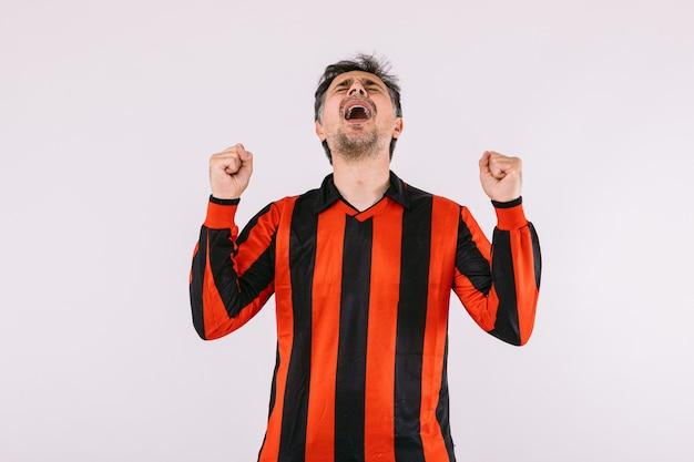 Voetbalfan draagt een zwart en rood gestreepte trui, balt zijn vuisten en schreeuwt juichend voor zijn team op witte achtergrond