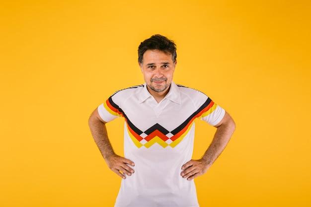 Voetbalfan, gekleed in een wit t-shirt met zwarte, rode en gele strepen, poseert met zijn armen om zijn middel