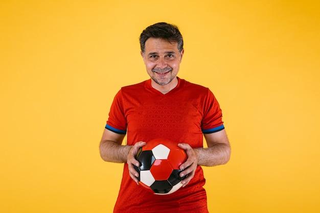 Voetbalfan met rode trui en een bal in zijn handen