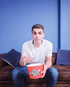 Voetbalfan op de bank met popcorn