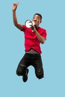 Voetbalfan springen op blauwe achtergrond. de jonge afroman als voetbalfan met megafoon