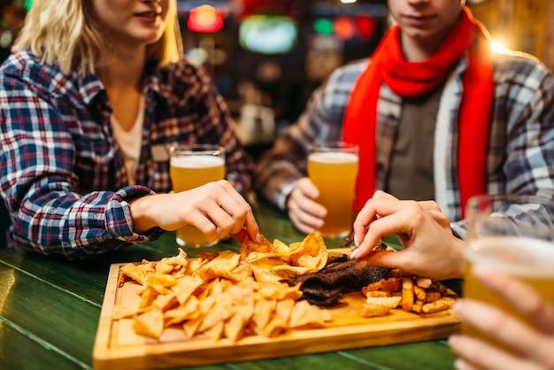 Voetbalfans drinken bier en eten chips aan tafel in de sportbar.
