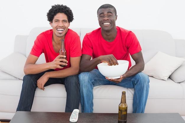 Voetbalfans in rode zitting op laag met bier en popcorn