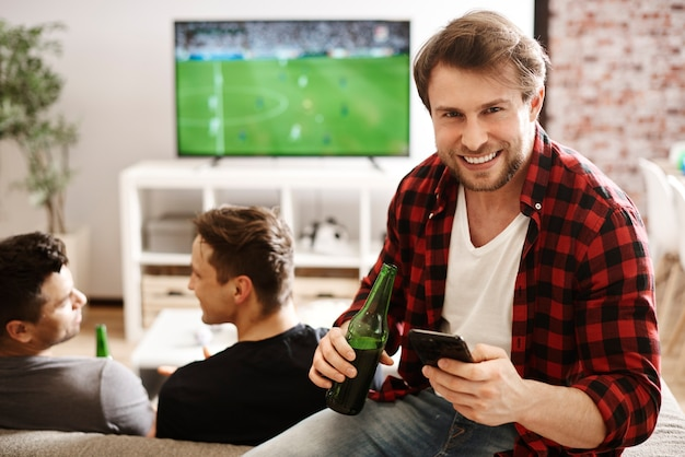 Voetbalfans met mobiele telefoon en bier
