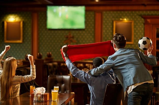 Voetbalfans met rode sjaal kijken naar spelvertaling, vrienden in de bar. groep mensen ontspannen in pub, nachtlevensstijl, vriendschap, sportviering