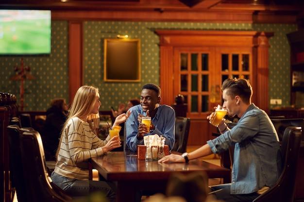 Voetbalfans met rode sjaal kijken naar spelvertaling, vrienden in de bar