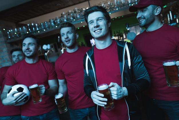 Voetbalfans vieren en drinken bier.
