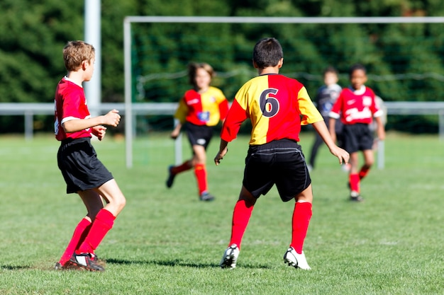 Voetbaljongen die met de nummer 6 t-shirt spelen