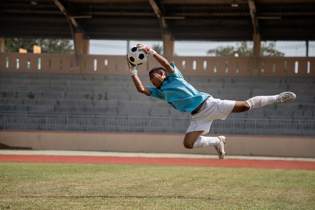 Voetbalkeeper in actie betreffende het voetbalstadion