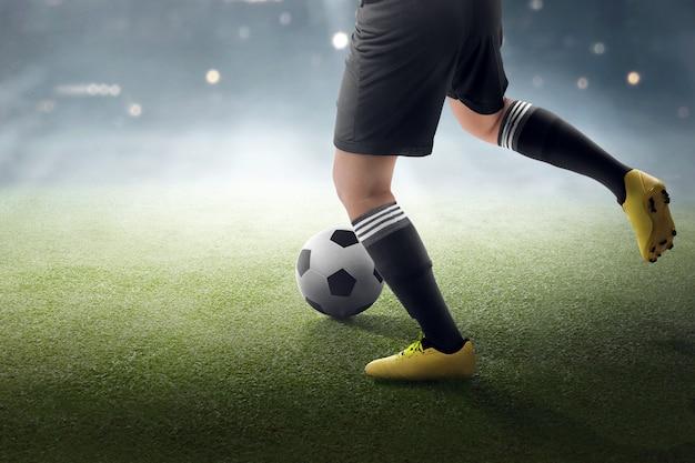 Voetballer die de bal probeert te schoppen