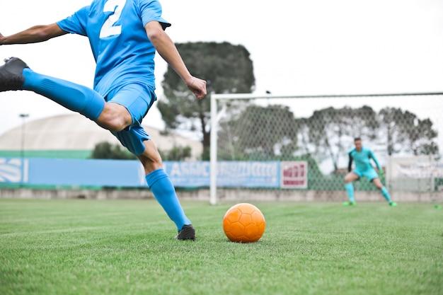 Voetballer die de bal schopt