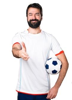 Voetballer die een voetbal houdt die een overeenkomst maakt