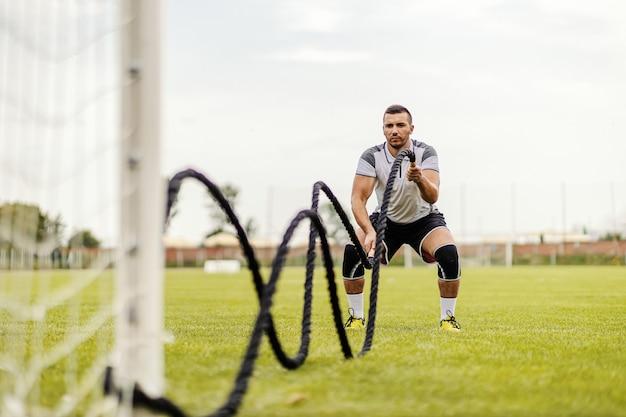 Voetballer die oefeningen op het veld doet. hij doet oefeningen met gevechtstouwen.