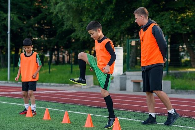 Voetballer die onder oranje kegels op stadion tijdens training loopt