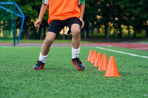 Voetballer die onder plastic oranje kegels op kunstmatig stadion loopt