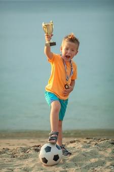Voetballer jongen op het strand het verhogen van een gouden trofee