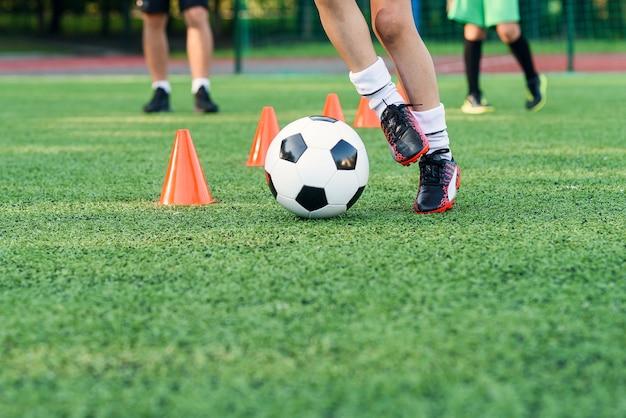 Voetballer met bal onder oranje kegels
