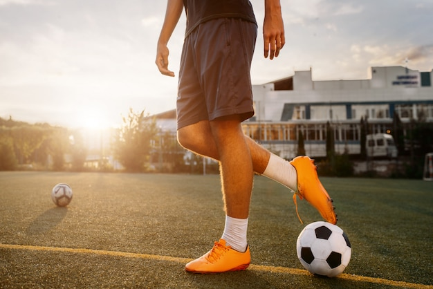Voetballer met bal op het veld bij zonsopgang. voetballer op buitenstadion, training voor wedstrijd, voetbaltraining