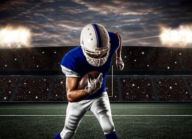 Voetballer met een blauw uniform dat op een stadion loopt