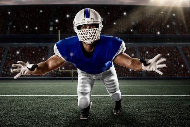 Voetballer met een blauw uniform die een uitrusting op een stadion maakt