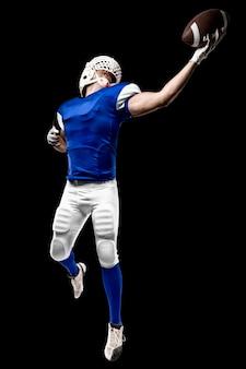 Voetballer met een blauw uniform die een vangst op een zwarte muur maakt