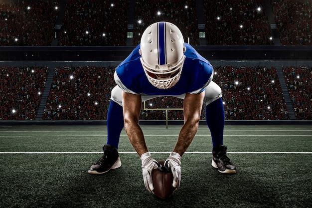 Voetballer met een blauw uniform op de scrimmagelijn op een stadion