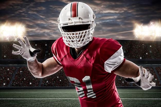 Voetballer met een rood uniform die een uitrusting op een stadion maakt.