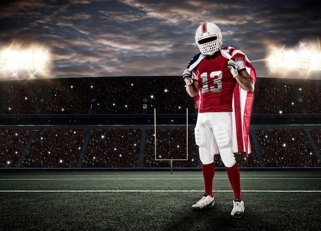 Voetballer met een rood uniform en een amerikaanse vlag, op een stadion.