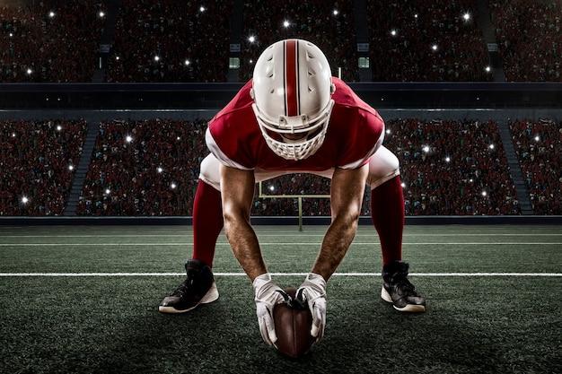 Voetballer met een rood uniform op de scrimmagelijn, op een stadion.