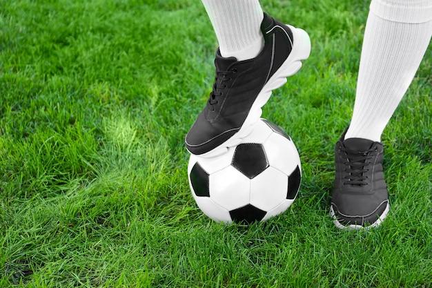 Voetballer met voetbal op groen gras buitenshuis