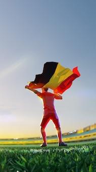 Voetballer na kampioenschap van het winnaarspel houdt de vlag van belgië vast. veelhoekstijl