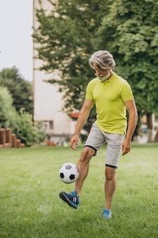 Voetballer van middelbare leeftijd met voetbalbal