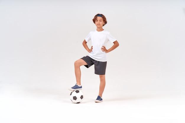 Voetballer van volledige lengte van een gelukkige tiener die met voetbal naar de camera kijkt en