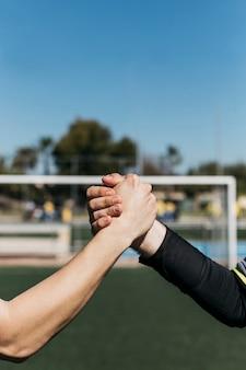 Voetballers die handen schudden