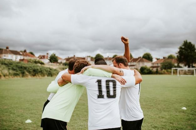 Voetballers die voor een gelijke huddling